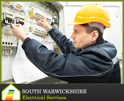 electrician with a hard hat testing a fuse box